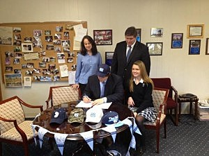 Brad Helson signs agreement with the University of North Carolina as his family looks on.