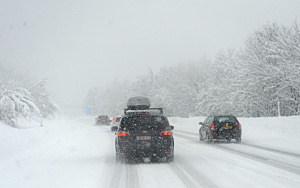 Cars drive on snowy roads