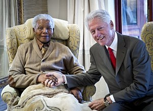 former President Bill Clinton (R) poses with former South African President Nelson Mandela on the eve of his 94th birthday