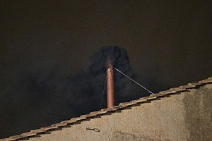 Black smoke billows out from a chimney on the roof of the Sistine Chapel