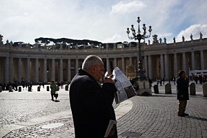 A man reads a paper in St Peter's Square the morning after the election of Pope Cardinal Jorge Mario Bergoglio of Argentina