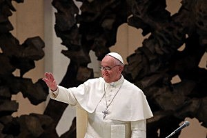 Newly elected Pope Francis gestures after entering the hall as he holds his first audience with journalists and media inside the Paul VI hall