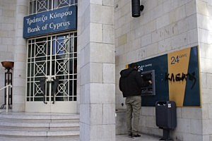 A man uses an ATM machine of the Bank Of Cyprus