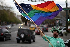 Same-sex marriage supporter Nikolas Lemos waves a Pride flag during a rally in support of marriage equality in San Francisco