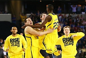 The Michigan Wolverines celebrate their 87 to 85 win over the Kansas Jayhawks in overtime