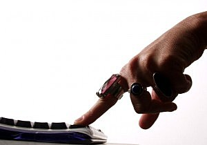 A woman's finger pressing a keyboard
