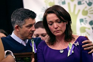 Ian Hockley and Nicole Hockley, parents of Sandy Hook massacre victim Dylan Hockley (6), embrace during a press conference with fellow parents of victims on the one month anniversary of the Newtown elementary school  shooting