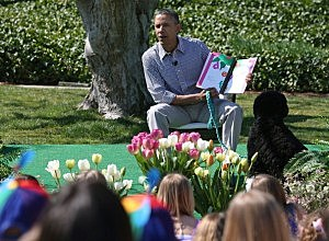 President Barack Obama sits with his dog Bo and reads a book to children during the annual Easter Egg Roll on the White House tennis court