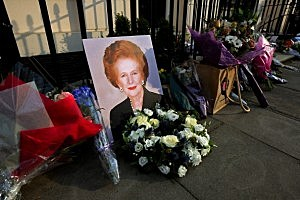 A portrait of former Prime Minister Margaret Thatcher is left next to floral tributes outside her residence in London's Chester Square