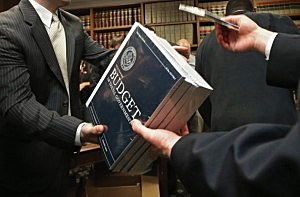 Senate Budget Committee staff members hand out copies of the Obama Administration's proposed FY 2014 federal budget