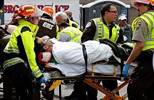 A man is loaded into an ambulance after he was injured by one of two bombs exploded during the 117th Boston Marathon near Copley Square