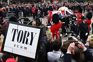 A protest sign as the coffin is carried on a horse drawn gun carriage during the Ceremonial funeral of former British Prime Minister Baroness Thatcher at Ludgate Hill