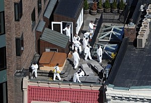 Crime scene investigators inspect a rooftop above the sight of a bombing on Boylston Street