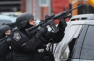 A Boston SWAT team member takes up as posistion as they search for 19-year-old bombing suspect Dzhokhar A. Tsarnaev