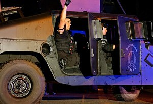 A member of the North Metro SWAT team raises his fist while leaving the scene near Franklin Street