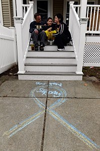 "Deanna Finn (R) hugs her son Sean Jr. on the steps of their house with her husband Sean Finn looking on after they drew a chalk ribbon with the wards ""Boston Strong""  near Franklin Street in Watertown, Mass"