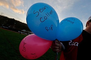A Watertown resident holds up a collection of balloons, each with a name of those killed in the last week by the Boston Marathon suspected bombers, during a candlelight vigil at Victory Park on April 20, 2013 in Watertown, Massachusetts.