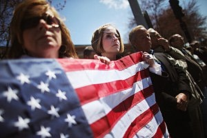 Jaime Caputo (C) holds an American flag outside the funeral for 29-year-old Krystle Campbell in Medford, Massachusetts