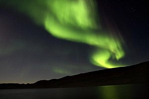 he Aurora Borealis glows over a lake near the Greenland town of Kangerlussuaq
