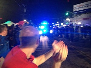 Crowds in Watertown cheer the police car carrying suspect