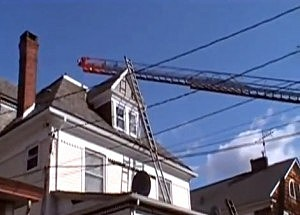 Fire ladder reaches to the top of a an apartment building in Hamilton after a roof collapse