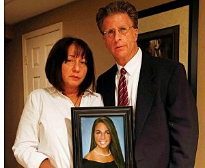Paige Aiello's parents Robin and Christopher hold her portrait in a picture sent to Townsquare Media