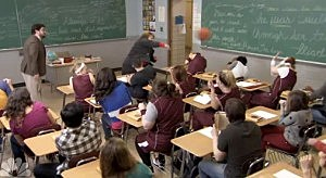 Coach Kelly hurls basketballs at students in a classroom