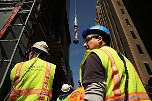Construction workers watch as the 408-foot spire is hoisted onto a temporary platform on the top of One World Trade Center