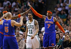 Carmelo Anthony #7 of the New York Knicks celebrates with teammates Kenyon Martin #3 and Jason Kidd #5 as Courtney Lee #11 of the Boston Celtics walks toward the bench