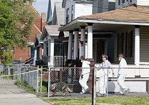 Police in protective suits investigate houses down the street from the house where three women were held captive for close to a decade