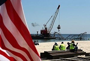 Workers on lunch break watch removal of the Star Jet roller coaster that has been in the ocean for six months after the Casino Pier is sat on collapsed when Superstorm Sandy hit. (Photo by Mark Wilson/Getty Images)