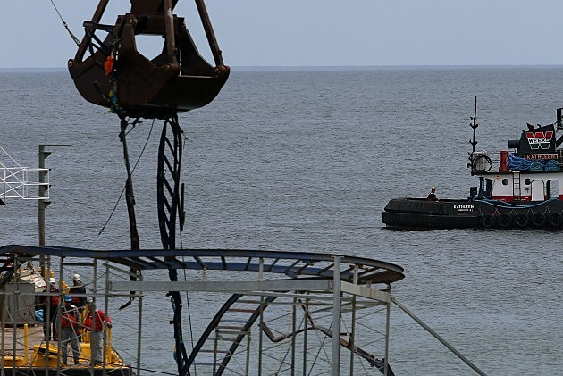A large crane demolishes the Star Jet roller coaster that has been in the ocean since Sandy hit the Jersey Shore (Getty Images)