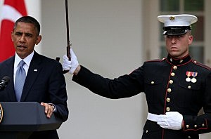 President Barack Obama (L) speaks as a U.S. Marine holds an umbrella over him, during a news conference with Prime Minister Recep Tayyip Erdogan of Turkey (not shown), in the Rose Garden