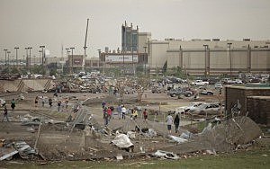 People walk through a damaged area near the Moore Warren Theater