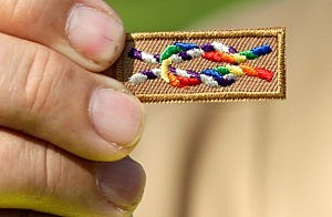 """A member of Scouts for Equality holds an unofficial knot patch incorportating the colors of the rainbow, a symbol for gay rights, during a rally to call for equality and inclusion for gays in the Boy Scouts of America as part of the """"Scouts for Equality Day of Action"""""""
