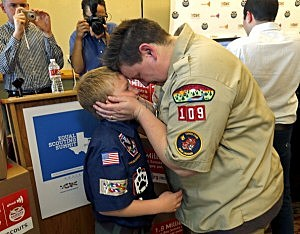 Jennifer Tyrrell of Bridgeport, Ohio, a Cub Scout den leader who was kicked out in 2012 for being openly gay, embraces her son Cruz Burns, 8, before a news conference at the Great Wolf Lodge May 23, 2013 in Grapevine, Texas