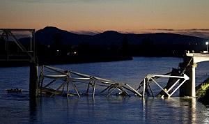 A boat cruises past the scene of a bridge collapse on Interstate 5 near Mt. Vernon, Washington