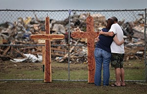 Deana Sanderson (L) and Timothy Gansman embrace as they view a memorial in front of the destroyed Plaza Towers Elementary School