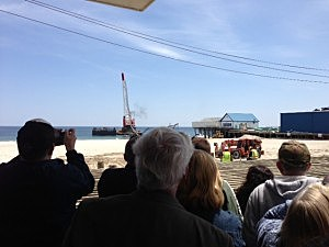 People watch the removal of the Jet Star coaster from the Atlantic Ocean