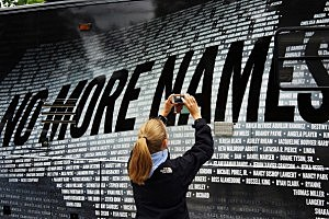 Lindsay Knauf takes a picture of a bus bearing some of the over 6,000 names of people killed by gun violence since the massacre in Newtown at a remembrance event on the six month anniversary of the massacre at Sandy Hook Elementary School