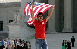 An advocate for same sex marriage rights runs from the Supreme Court waving an American flag following favorable rulings issued by the court