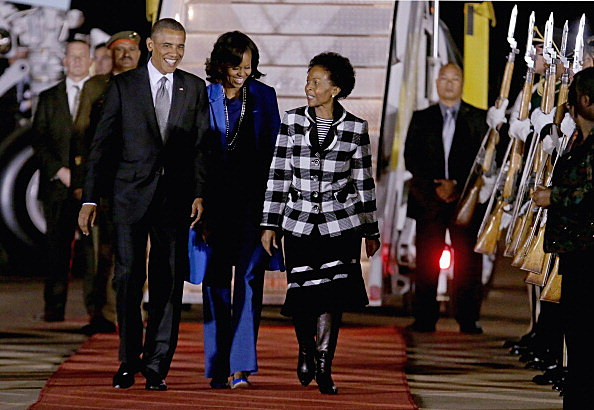 President Barack Obama (L) and first lady Michelle Obama (C) are greeted by Minister of International Relations and Cooperation Maite Mkoana-Mashabne after arriving at Waterkloof Air Force Base