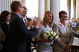 Supporters applaud as same-sex couple Sandy Stier (2R) and Kris Perry (R) prepare to get married at San Francisco City Hall