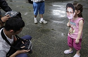 : A young girl holds up a cut out image of Edward Snowdens face at the start of the protest rally to support Edward Snowden in Hong Kong