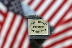 The exterior sign of Station 7 is seen through American flags hung on a fence