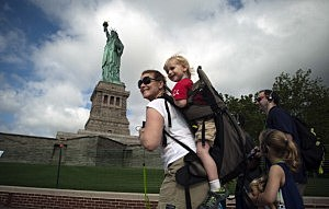 A family walks by the Statue of Liberty on the first day it is open to the public after Hurricane Sandy