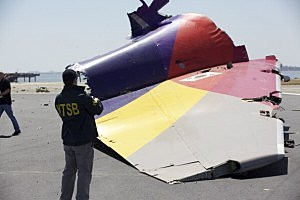 an NTSB investigator documents the tail section of the Asiana Airlines flight 214 wreckage