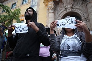 Demonstrators James Alvarez, 34, and Yesenia Mena, 29, hold signs in front of the Freedom Tower in downtown Miami
