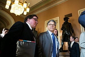 Sen. Al Franken (D-MN) walks with an aide to a Senate joint caucus meeting