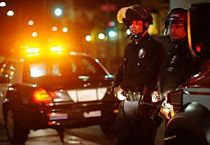 Los Angeles Police Department officers in riot gear look at protestors in the streets around Leimert Park following a prayer vigil against the acquittal of George Zimmerman